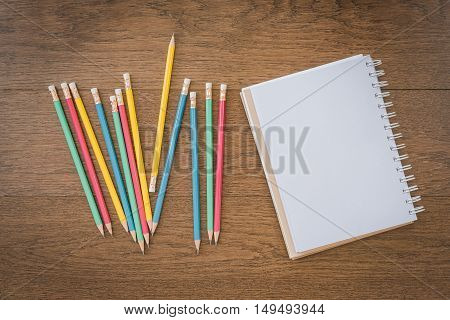 Multicolor Pencils And Blank Notebook On Wooden Background