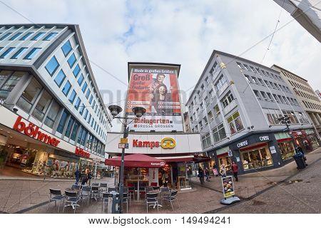 ESSEN, GERMANY - MARCH 07, 2016: Few pedestrants walk through a shopping street after rain