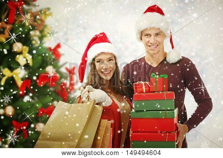 Young couple with purchases and decorated Christmas tree on blurred lights background. Christmas holiday concept.