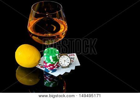 Cards with colorful chips to play poker and snifter of brandy with lemon