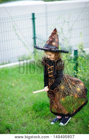 Preparation for Halloween. The girl in a suit of the evil witch pretends that she flies on the broom. The girl is dressed in a black-orange dress and a big hat. She has a good mood. Children adore Halloween.