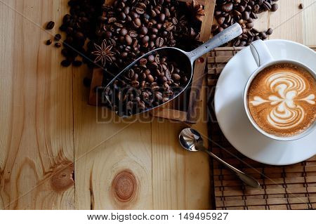 Cup of coffee beans and scoop on old rusty background