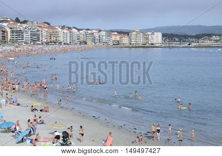 SANGENJO, SPAIN - AUGUST 8, 2016: Beach crowded of people in Sangenjo a popular tourism destination in Galicia Spain.