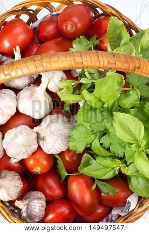 basket with tomatoes green basil and garlic