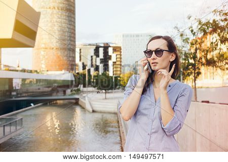 Young smiley Caucasian business woman is talking on the smart-phone near skyscrapers. Nice female with long brown hair is standing on the street and  having telephone conversations. Flare light