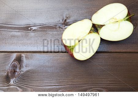 Two halves apple pieces of a red apple on the table red apples on a brown wooden background.