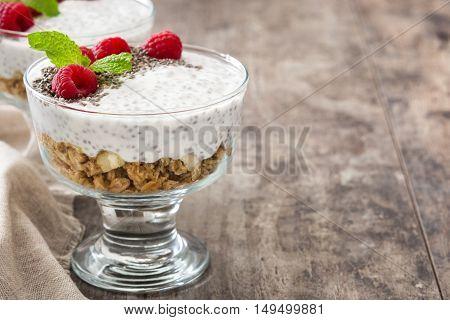 Chia yogurt with raspberries on wooden background