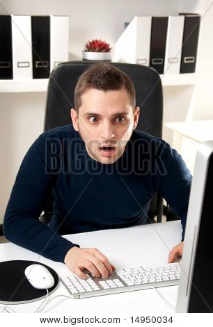 Young Man Surprised In Front Of His Computer