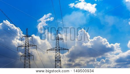 two transmission towers of a transformer station and a blue sky. Concept for energy and technology