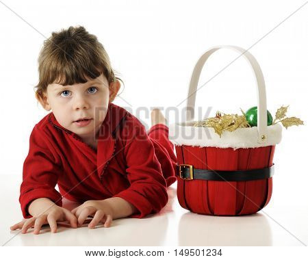 An adorable blue-eyes, brunette preschooler in her red pajamas laying on her belly by a basket of Christmas ornaments.  On a white background.