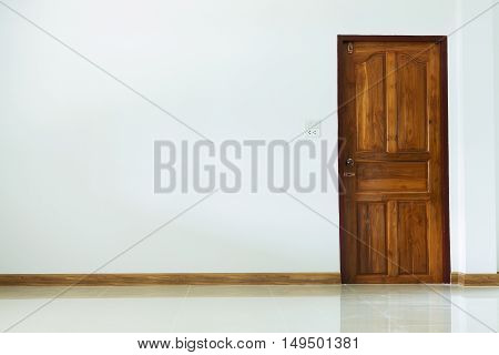 empty room interior with wooden door and white mortar wall