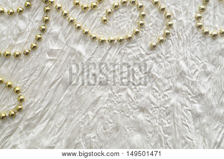 Wedding or celebration background with golden beads and white silk