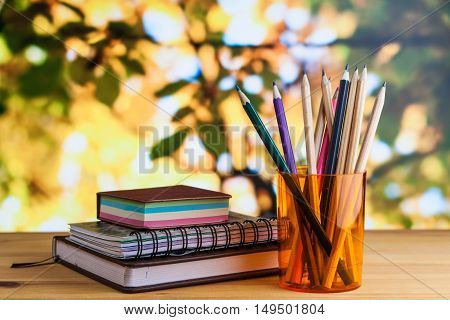 Stationery notepad address book notes pencils in a glass on a wooden table.