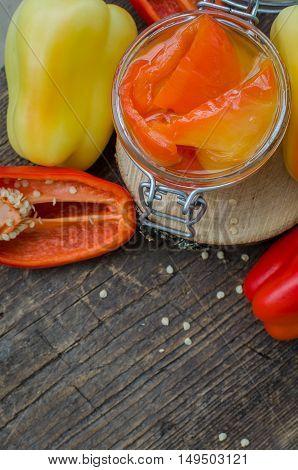 Bell pepper preserved in a glass jar with fresh peppers on old wooden background. Homemade marinated in oil red pepper. Glass jar with conserved roasted yellow and red paprika. Top view. Copy space.