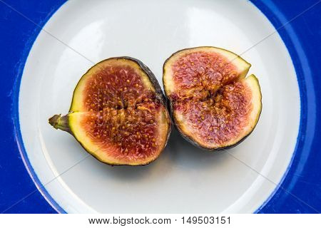 ripe fig sliced in half on a blue and white plate