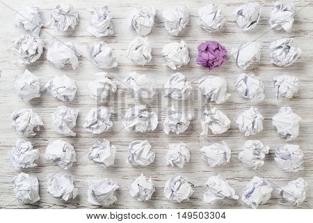 Set of crumpled white paper balls with one purple ball.