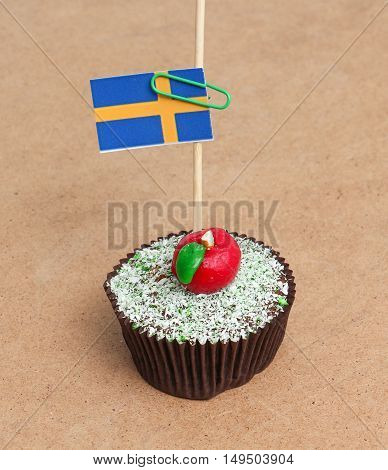 Flag of sweden on cupcake on wood background
