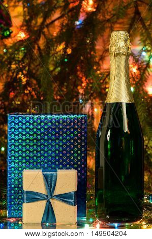 champagne and two gifts around the holiday bottle