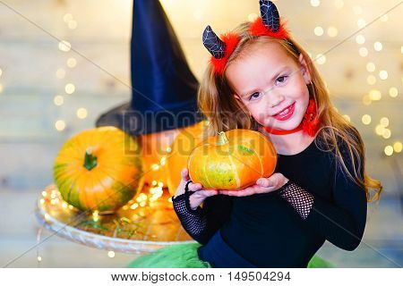 Happy deamon children during Halloween party playing around the table with pumpkins