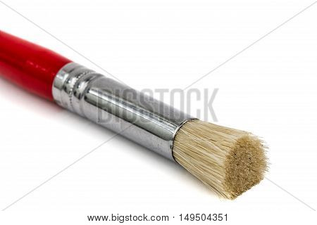 Red paint brush close-up isolated on white background