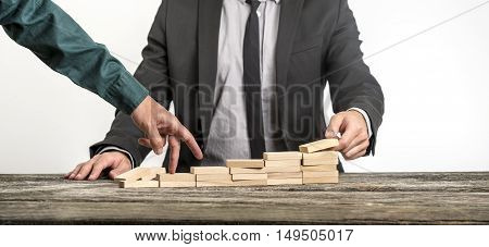 Unidentifiable businessmen stacking various flat wooden blocks for the other one to walk his fingers up towards career growth.