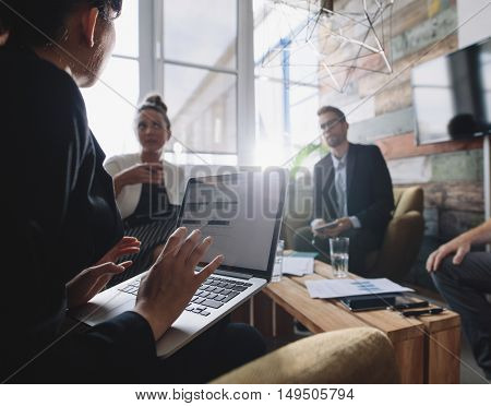 Business woman with laptop discussing business strategy with colleagues. Businesspeople having a meeting.