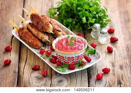 Homemade sauce dogberry with meat kebabs on wooden skewers.