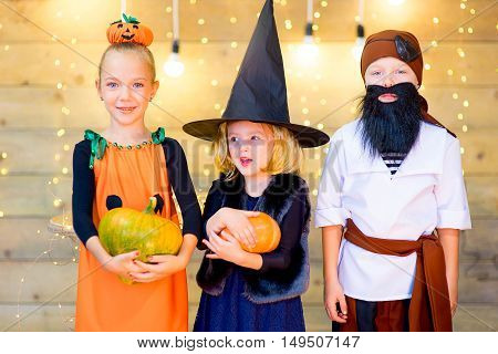 Happy group of pirate and witch children during Halloween party playing with pumpkins