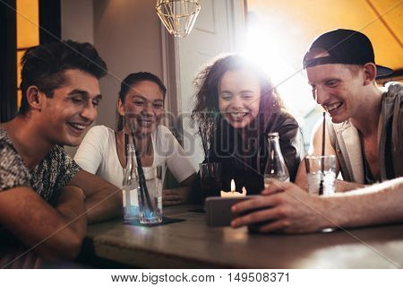 Group Of Friends In A Cafe Looking At Mobile Phone