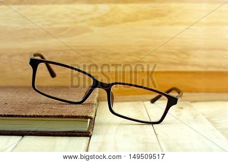 Glasses put brown color notebook on wooden table. Education concept.