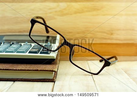 Glasses and on calculator and brown color notebook on wooden table. Education concept.