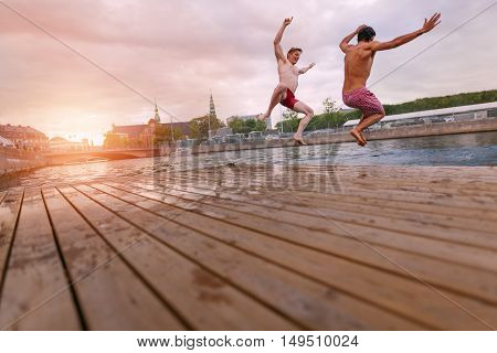 Young people jumping into lake in city. Two young friends enjoying a weekend.