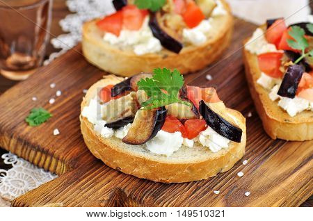 Crostini with soft cheese, eggplant, tomatoes and garlic.