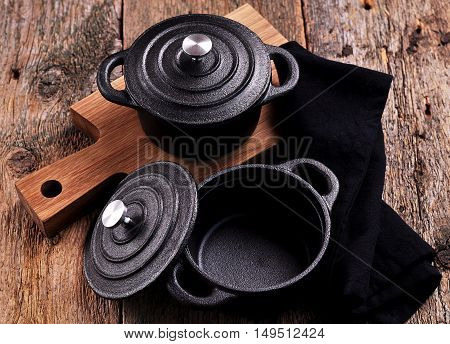 The small cast iron pan and cutting board on wooden background