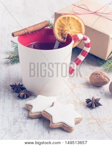 Homemade butter nuts star shaped cookies with icing pine orange slicescinnamon anise and walnuts over white wood background. A cup of berry tea and a gift box wrapped in kraft paper. Christmas decoration.