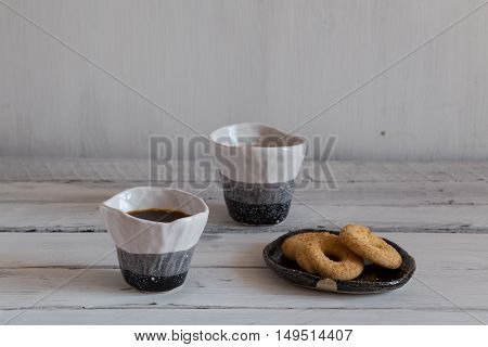 black and white hand-made ceramic tableware cookies on a ceramic plate a pair of clay cup on a white background tea with sweet dessert.