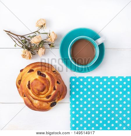 Blue cup of coffee on a saucer blue napkin in white pea cake with raisins and pressed a bouquet of roses on a white wooden surface.