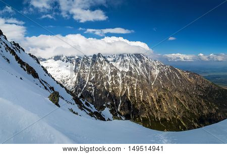 View of the rugged snow-capped mountains. Cloud on the mountain. Sky is clear. High Tatras Slovakia
