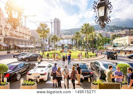 Monte Carlo, Monaco - June 13, 2016: Tourists make pictures near expensive cars and famous Casino building in Monte Carlo in Monaco. View from casino main entrance.