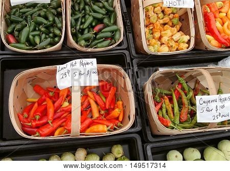 Baskets of colorful freshly harvested hot peppers in several varieties for sale a local farmer's market.