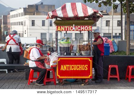 Lima, Peru - September 05, 2015: A man and a woman selling anticuchos with their food cart in the city center
