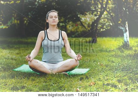 Young girl doing yoga in the beautiful wooden landscape