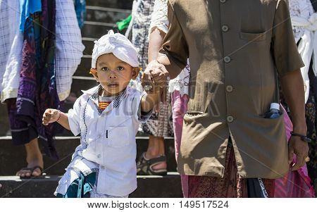 Bali Indonesia September 10th 2016: small indonesian boy walking down the temple stairs