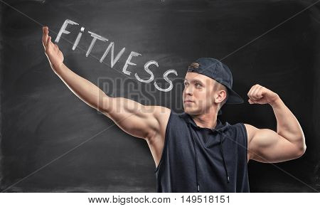 Athletic sportsman standing on the background with word 'fitness'. Healthy lifestyle. Workout to self-improvement. Fitness leads to perfection.