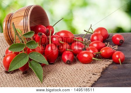 Fresh rosehip berries in a wooden bowl on the board with a burlap and a blurred background