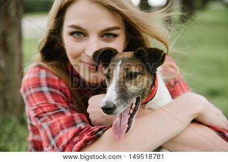 young pretty girl in red tartan shirt sit at the lawn and embrace her dog. Close up portrait.