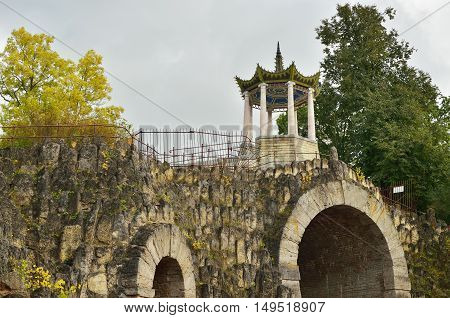 A large stone arch with Chinese gazebo on it.