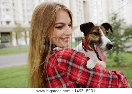 young pretty girl in red tartan shirt stand at public garden near buildings and hold her dog. Rear view. Close up.