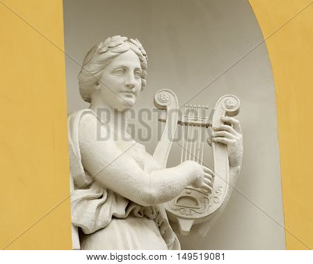 Sculpture of woman with lyre on the facade of the theater.