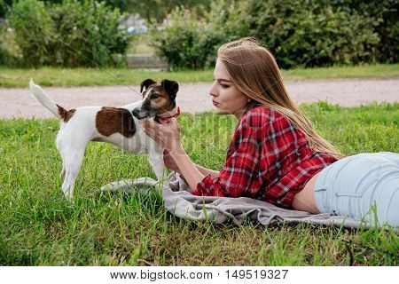 Smile pretty 20-25 years girl in tartan red shirt with long hair lies on the grass with her active foxterrier. side view